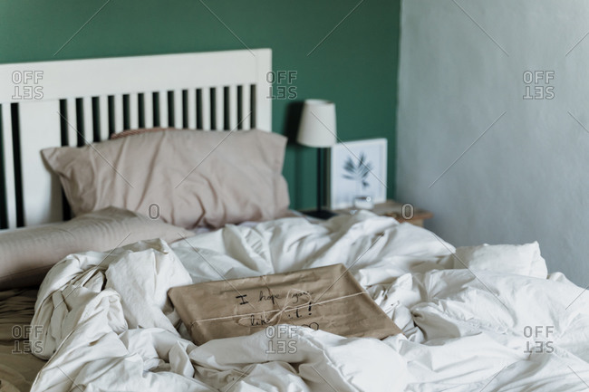 Gift wrapped in brown paper kept on messy bed at home