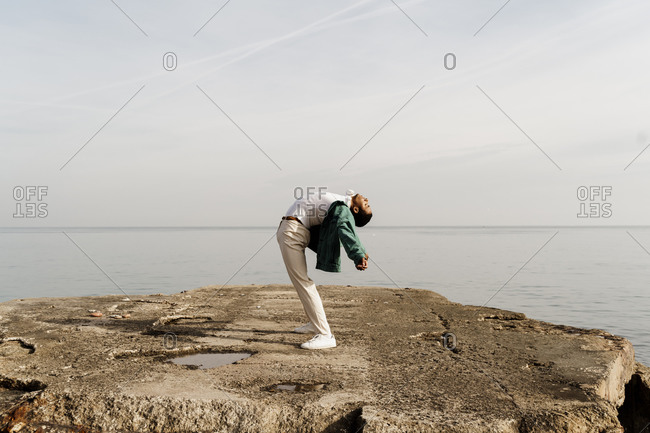 Young man bending back while standing on pier by sea