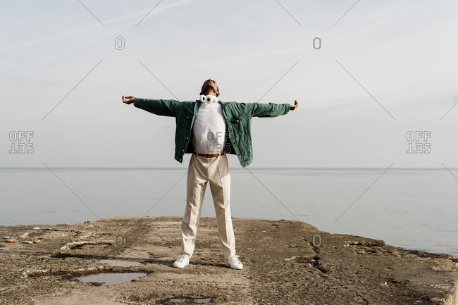 Carefree man with arms outstretched against sea on pier