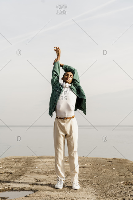 Young man with hand raised against sky standing on pier