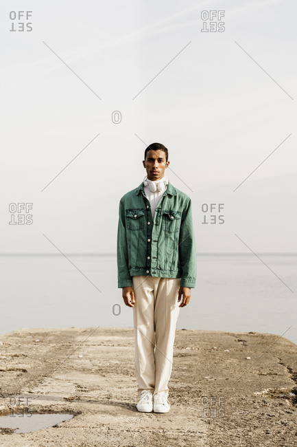 Young man standing on pier against sea