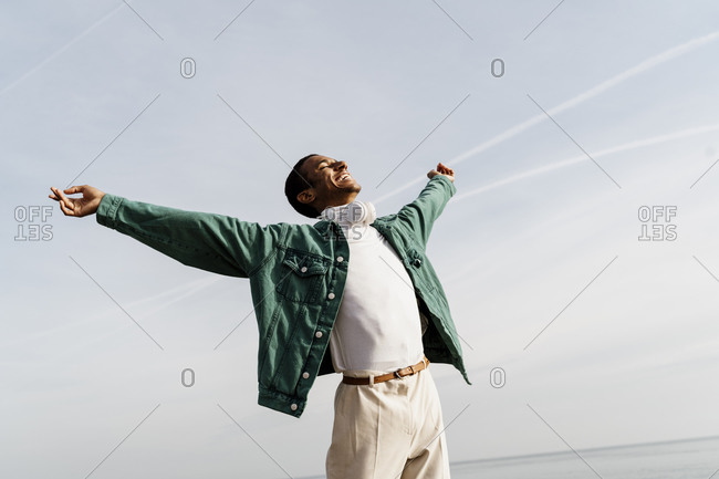 Happy carefree man with arms outstretched against sky