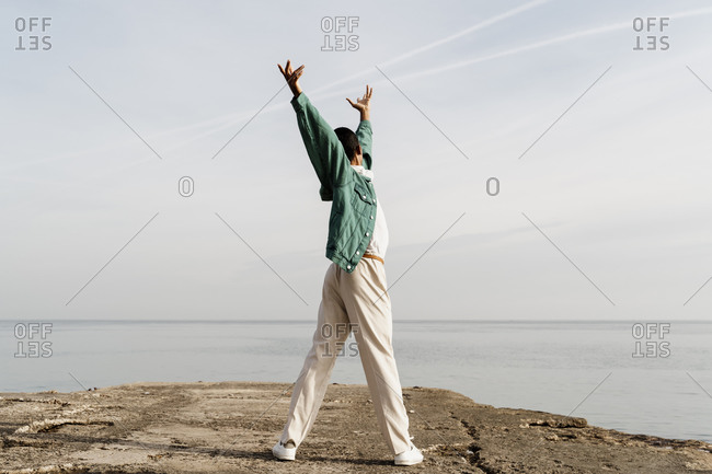 Young man dancing on pier in front of sky and sea