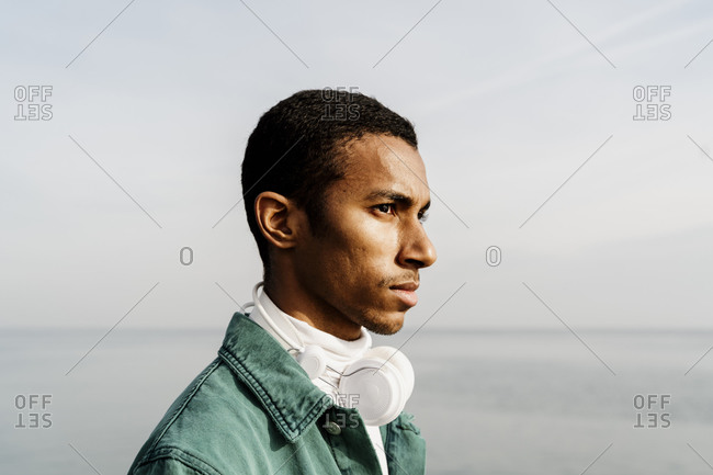 Young man with headphones looking away by sea and sky