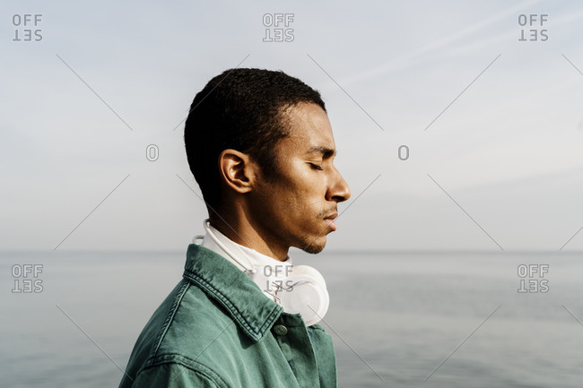 Man with eyes closed day dreaming by sea