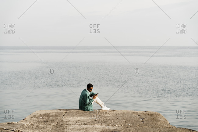 Young man using mobile phone while sitting on pier by sea and sky