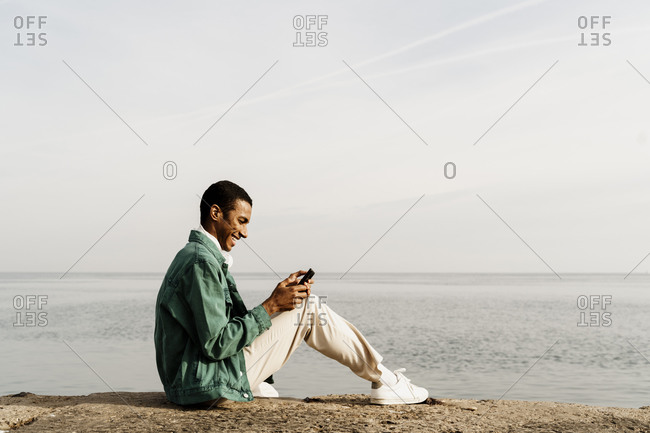 Happy man text messaging through smart phone while sitting on pier by sky and sea