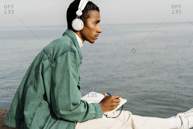 Thoughtful man with book looking away by sea