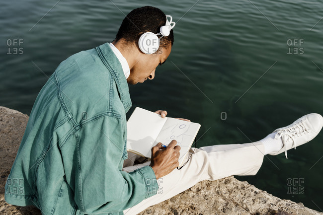 Man drawing in book while sitting on pier by sea