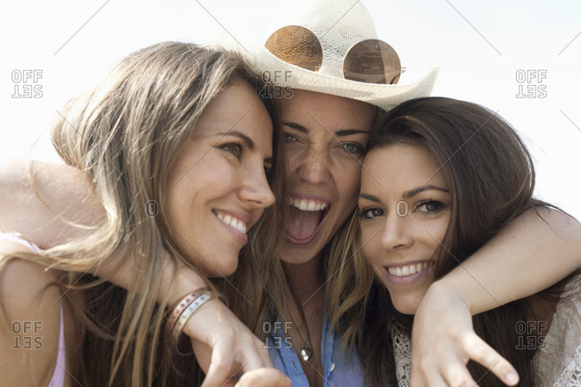 Excited woman embracing female friends during vacation