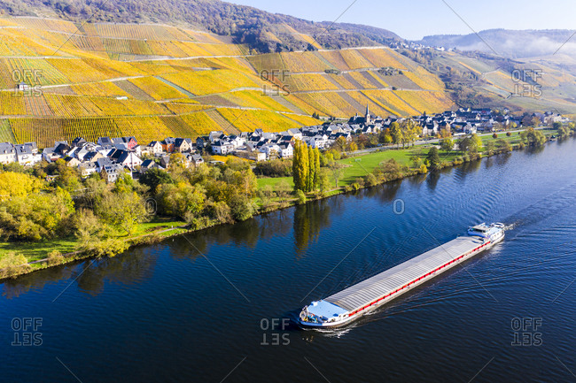 Germany- Rhineland-Palatinate- Bernkastel-Kues- Helicopter view of barge sailing along Middle Moselle with rural town in background