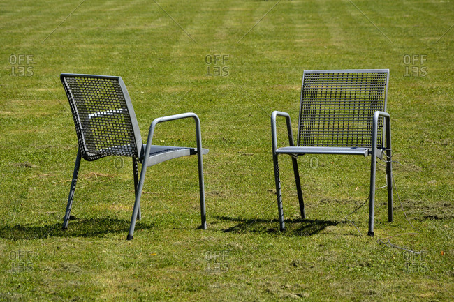 Two empty garden chairs standing on green lawn
