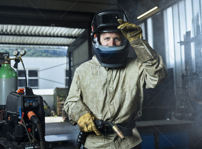 Manual worker wearing protective welding helmet holding welding machine while standing at factory
