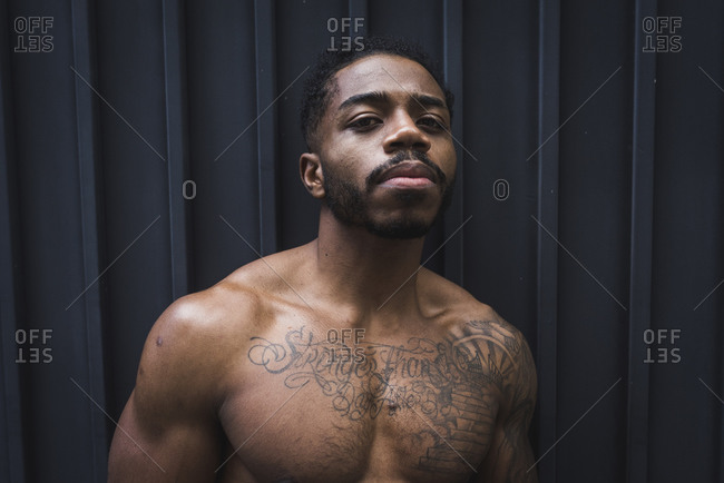 Confident sportsman with muscular build against corrugated wall