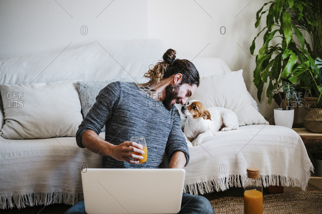 Man with juice and laptop smiling while looking at dog sitting on sofa at home
