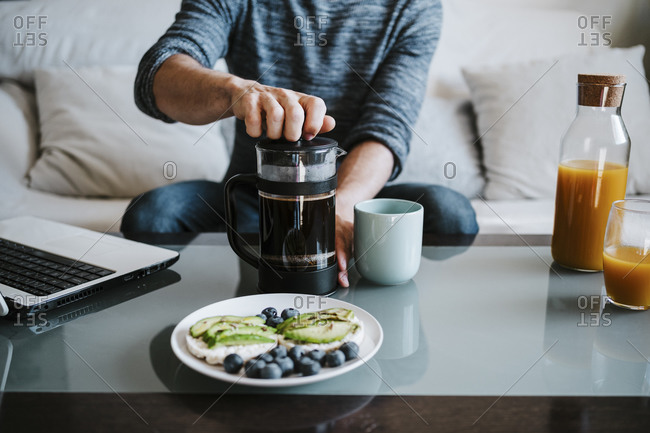 Man using coffee maker while having breakfast on table sitting at home