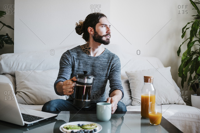 Man with coffee maker looking away while sitting by breakfast on table at home