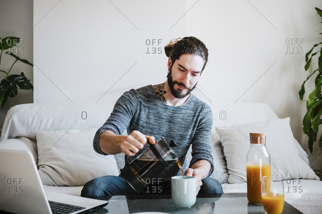 Man pouring coffee in coffee cup while sitting at home