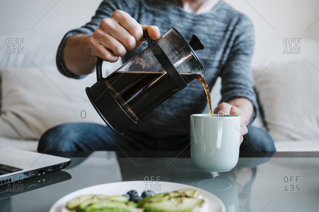 Man holding coffee maker while pouring coffee in coffee cup sitting at home