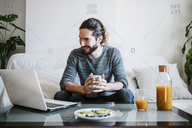 Young man with coffee cup using laptop while having breakfast sitting on sofa at home