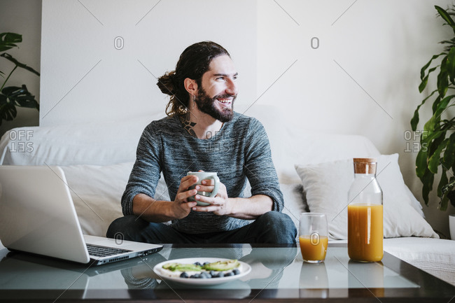 Smiling man with coffee cup looking away while having breakfast sitting on sofa at home