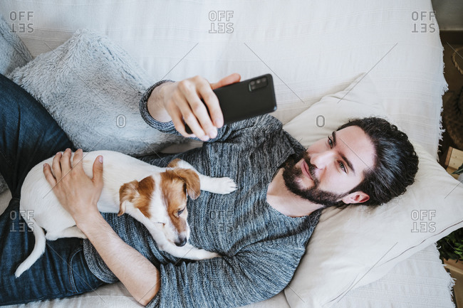 Young man taking selfie through mobile phone while lying on sofa with dog at home