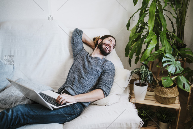 Smiling man with laptop looking away while sitting on sofa at home