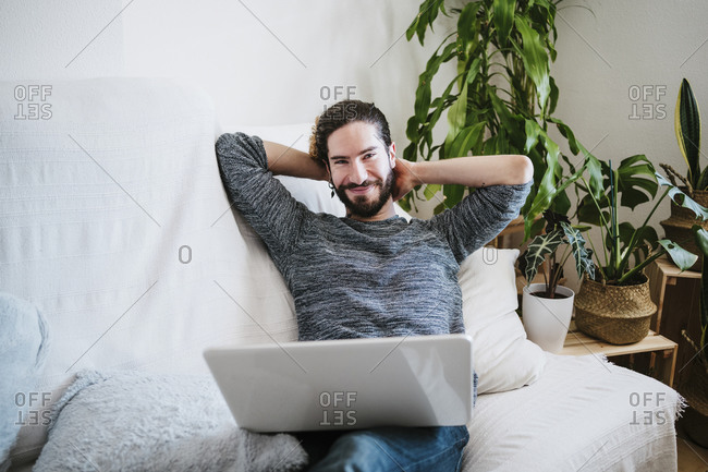 Smiling man with laptop relaxing while sitting on sofa at home