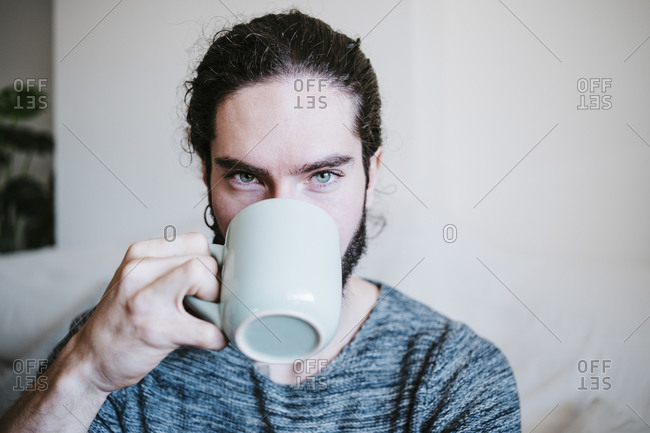 Man with blue eyes staring while drinking coffee sitting at home