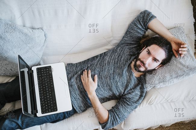 Man with laptop lying on sofa at home