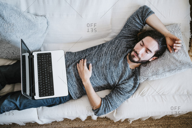 Man with laptop sleeping on sofa at home