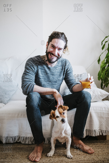 Smiling young man holding juice glass while sitting with dog on sofa at home