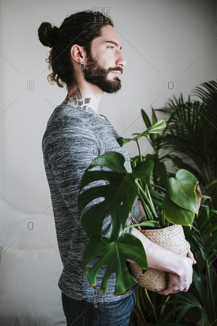 Young man looking away while holding Monstera plant at home