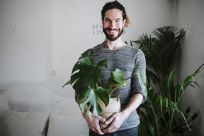 Young man smiling while holding Monstera plant at home