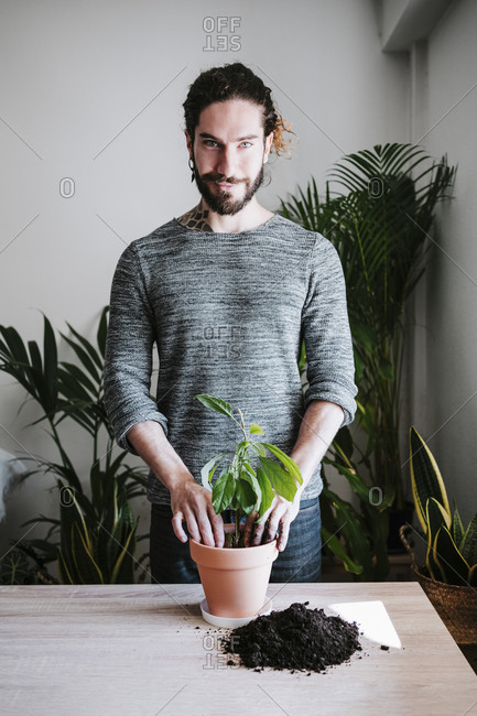 Young man planting avocado plant in flower pot while standing at home