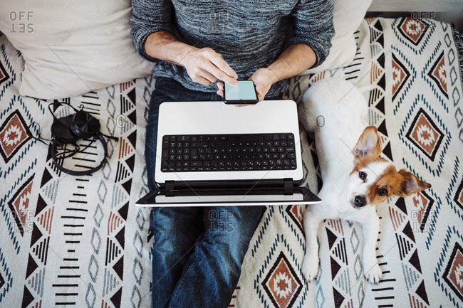 Man with laptop using mobile phone while sitting by dog on bed at home