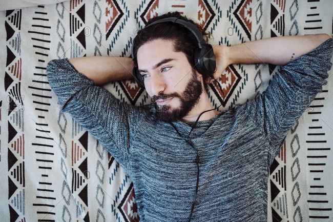 Man listening music through headphones while lying with hands behind head on bed at home