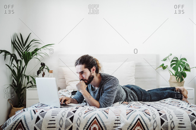 Young man working on laptop while lying on bed at home