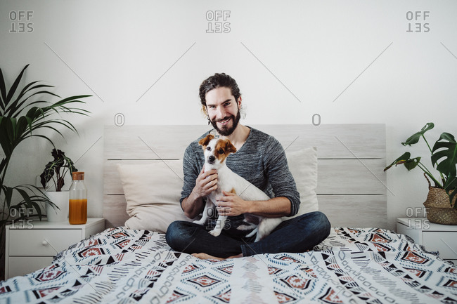 Handsome man sitting with dog on bed at home