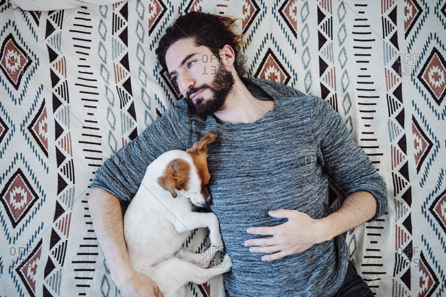 Thoughtful man lying on bed with dog at home