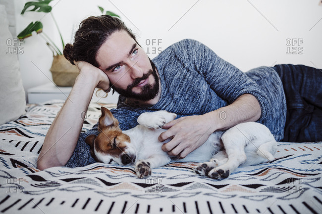 Thoughtful man looking away while lying with dog on bed at home