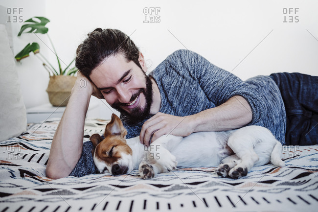 Young man smiling while looking at dog sleeping on bed at home