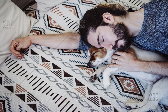 Man sleeping with dog on bed at home