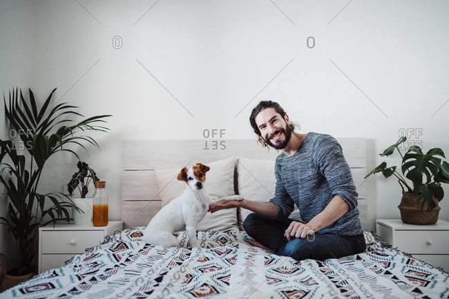 Handsome man playing with dog while sitting on bed at home