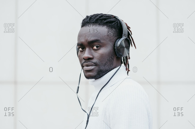 Young man listening music through headphones against white wall