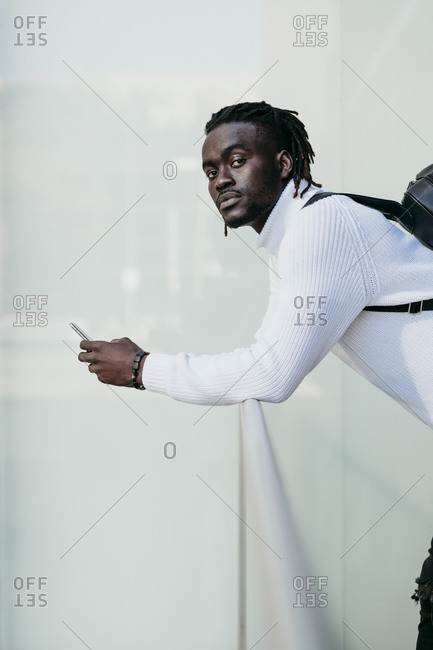 Confident businessman with mobile phone leaning on railing by white wall