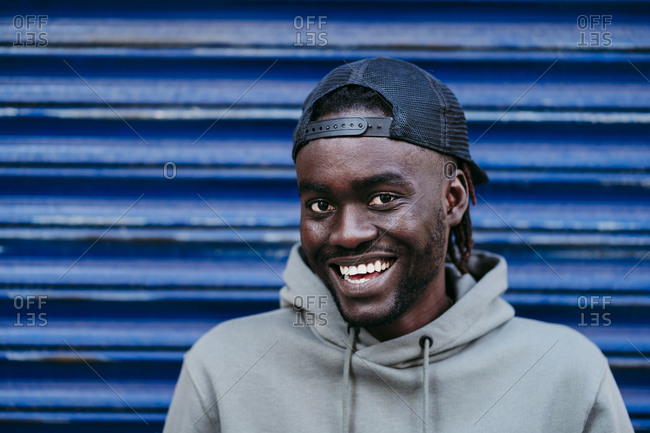 Cheerful young man in cap against blue corrugated wall