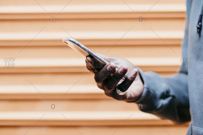 Young man with smart phone by brown corrugated wall