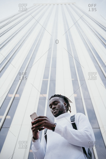 Young creative professional using smartphone against skyscraper in city