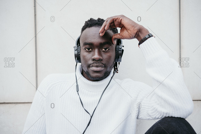 Confident young man listening music through headphones against white wall
